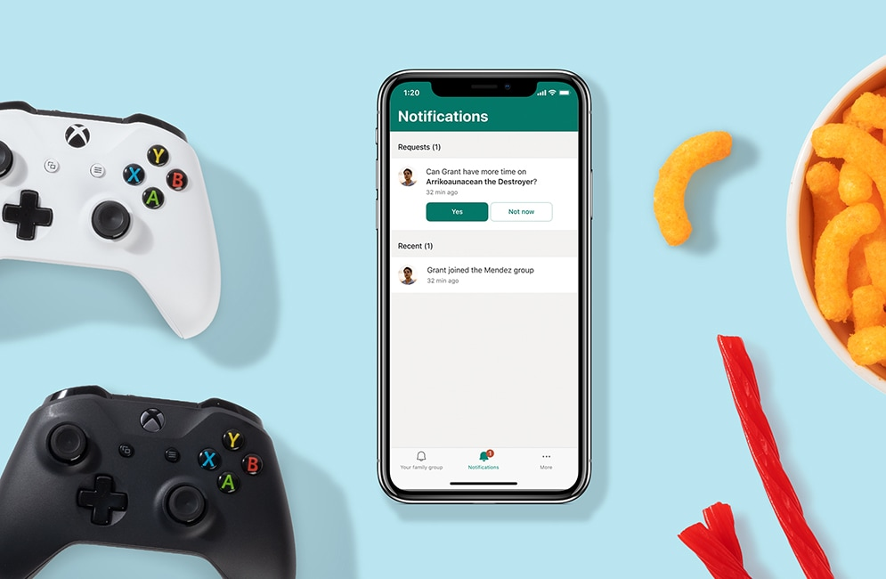 Mobile device lying on a flat surface next to Xbox game controllers and snacks. The device is displaying notifications in the Microsoft Family Safety app with a request for more time.