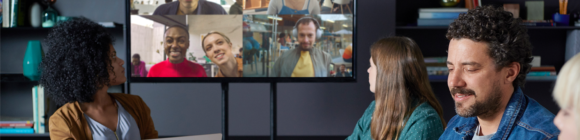 Four people having a meeting with five others joining via video, visible on the large screen at the front of the room
