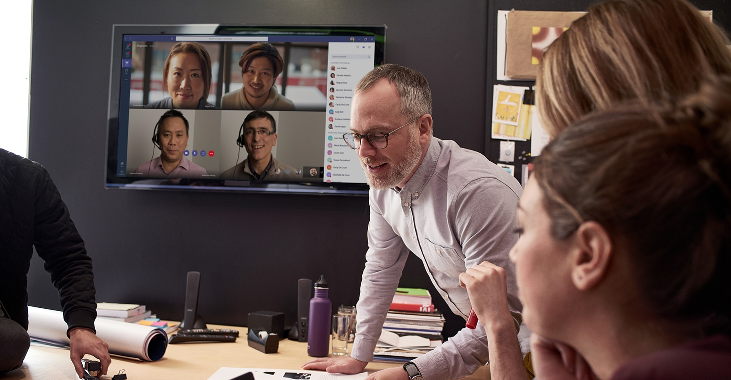 People participating in a meeting in person and online with Microsoft Teams