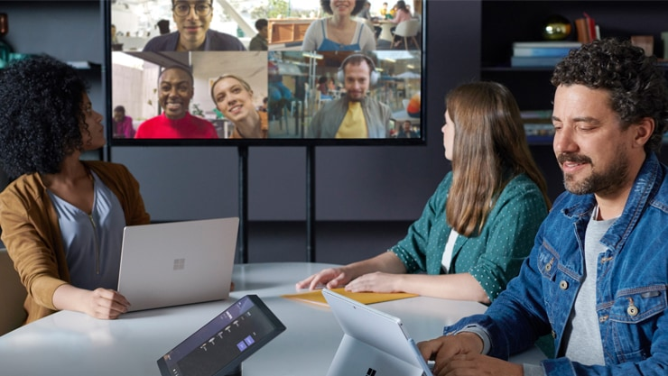 Three people in a conference room engaged in a Teams meeting displayed on a large monitor with another group of people who are all in different locations.