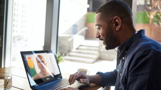 Person seated and looking at a Microsoft Surface in laptop mode