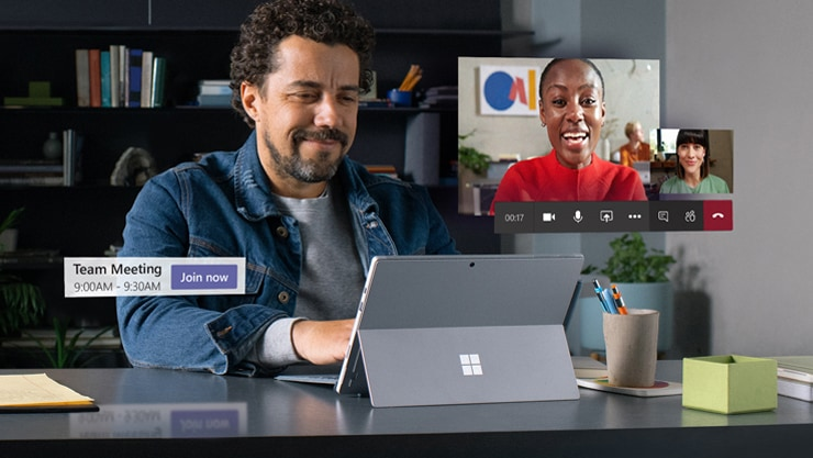Person sits at a desk and uses a Surface Pro laptop to join a Teams meeting. Two images of the other participants' videos float over the photograph conveying that they're all talking to each other.