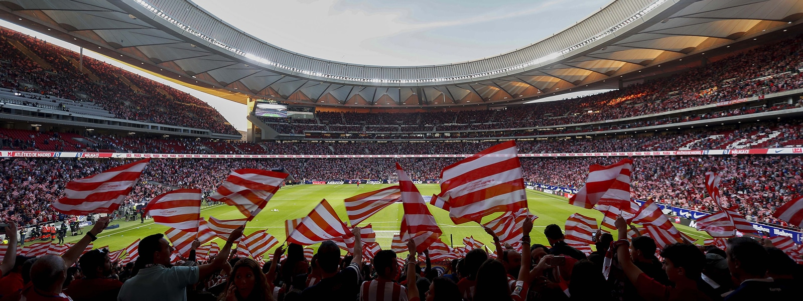 Fans waving flags in a packed Atletico Madrid stadium in Spain