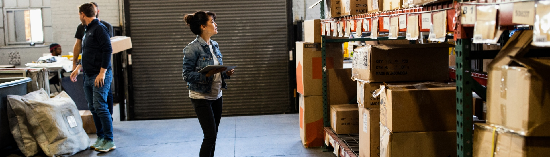 A person holding a tablet device, looking at boxes on a large shelf in a warehouse.
