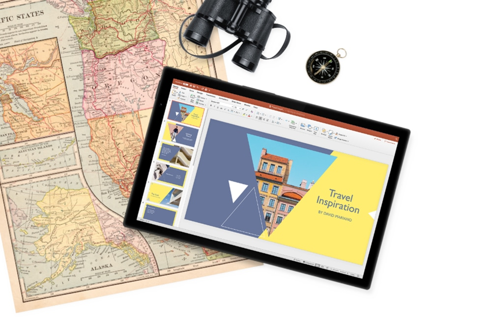 A tablet device displaying a presentation in PowerPoint. The tablet is lying on a map next to binoculars and a compass.