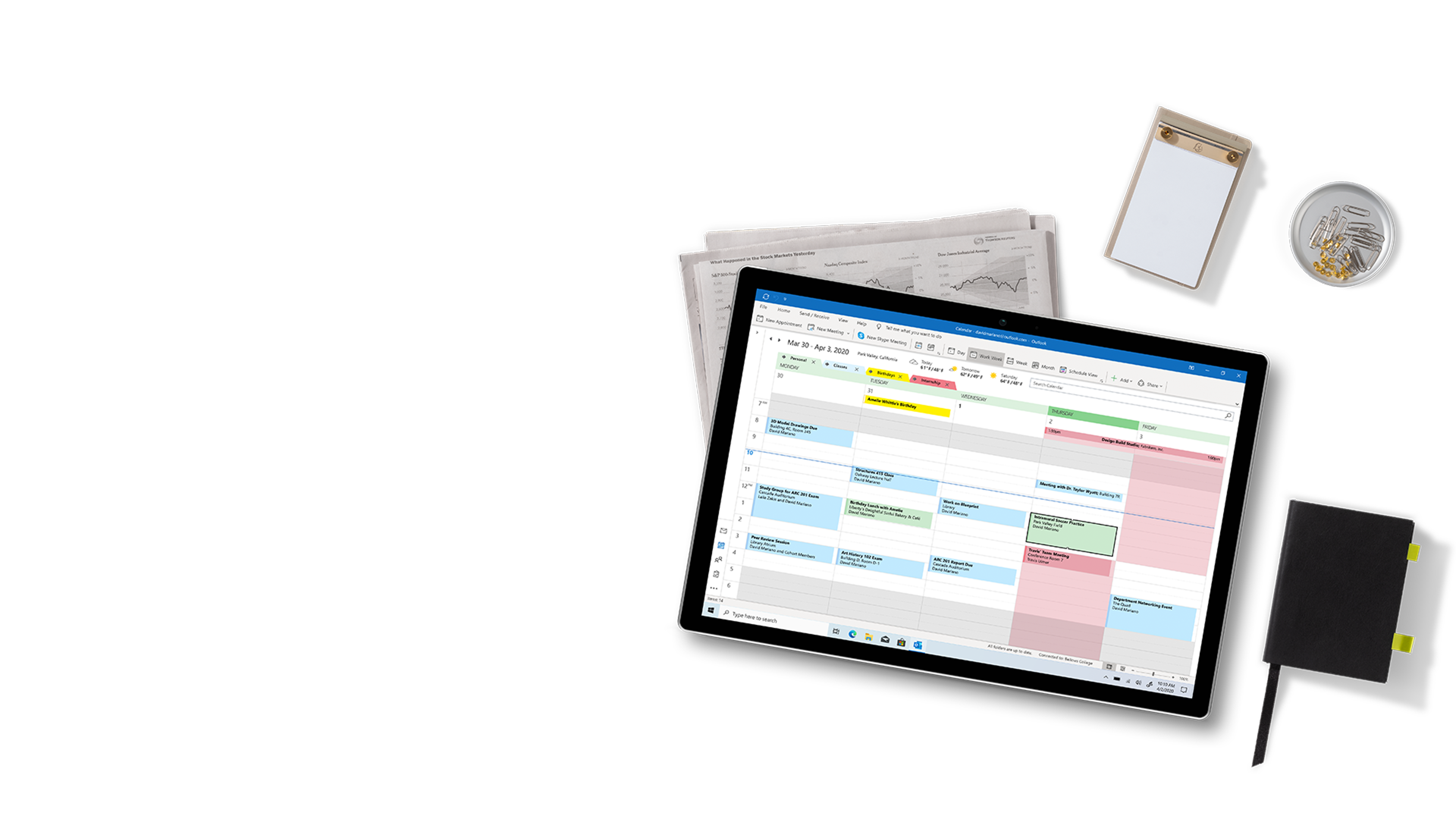 A tablet device displaying calendars in Outlook. The tablet is lying on folded newspaper, a notepad, a dish of fasteners, and a bound notebook.