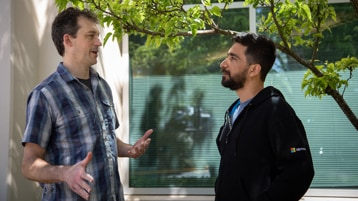 Frank Delia and Pranav Farswani talk animatedly in front of a Microsoft building.