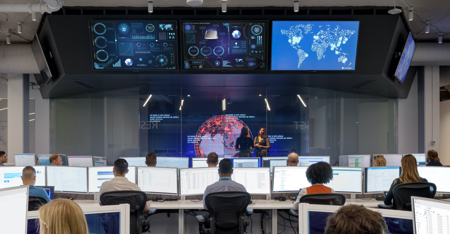 The Microsoft Cyber Defense Operations Center with security professionals working in front of arrays of display monitors