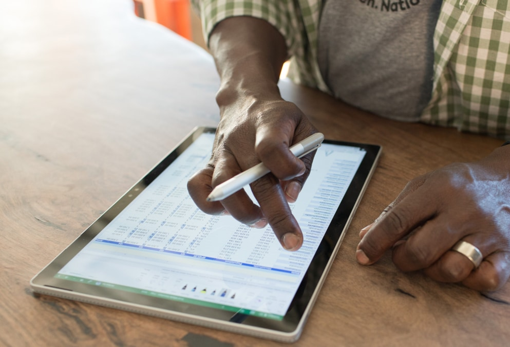Close-up of a person's hands working on an Excel spreadsheet on a tablet screen