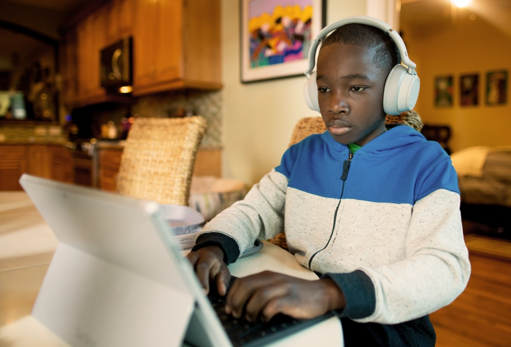 Young person wearing headphones and using a Surface Pro in laptop mode