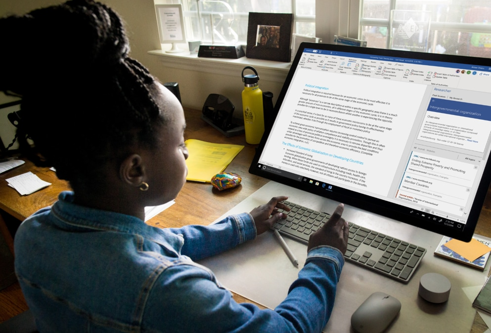 Young person using a wireless keyboard to work on a document in Microsoft Word on a large desktop monitor