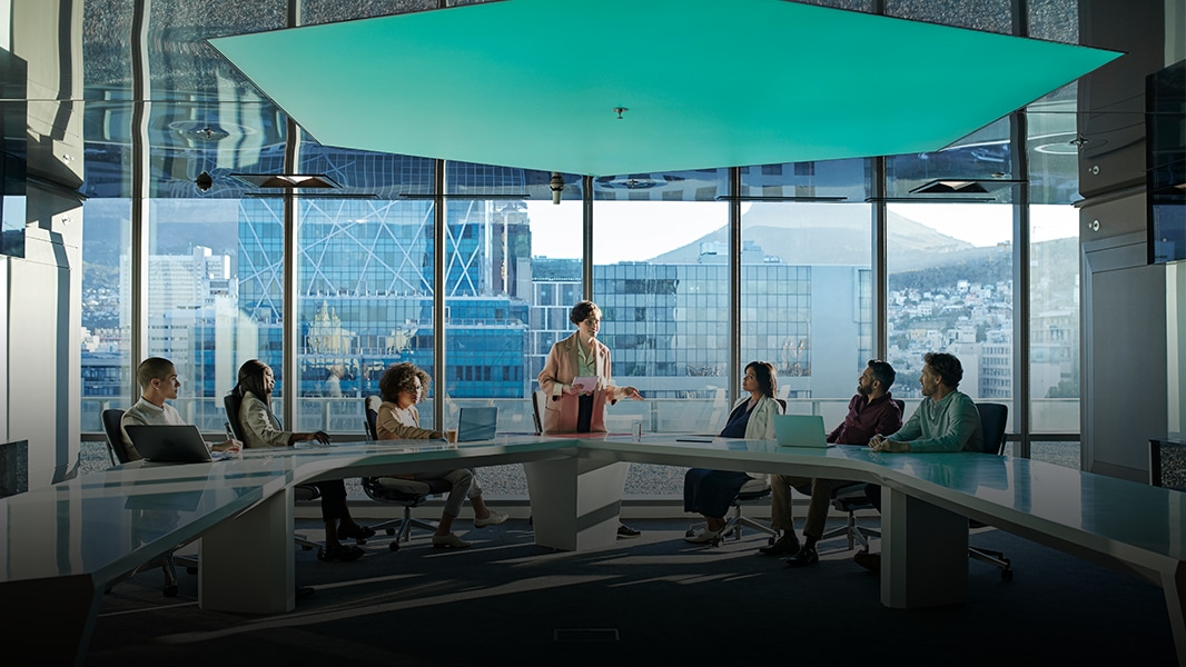 Coworkers meeting in a windowed conference room.