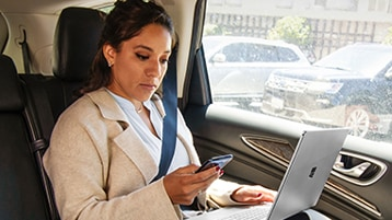 A person sitting in the back seat of a car using a laptop and looking at a mobile phone