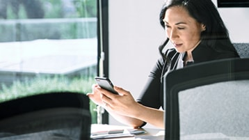 A person sitting at a conference table looking at a mobile phone
