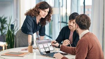 Una mujer y dos hombres con lap top trabajando en una mesa de oficina