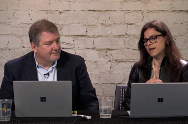 Two people with laptops seated at a table talking
