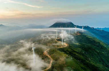 A wind farm in light clouds on top of a mountain