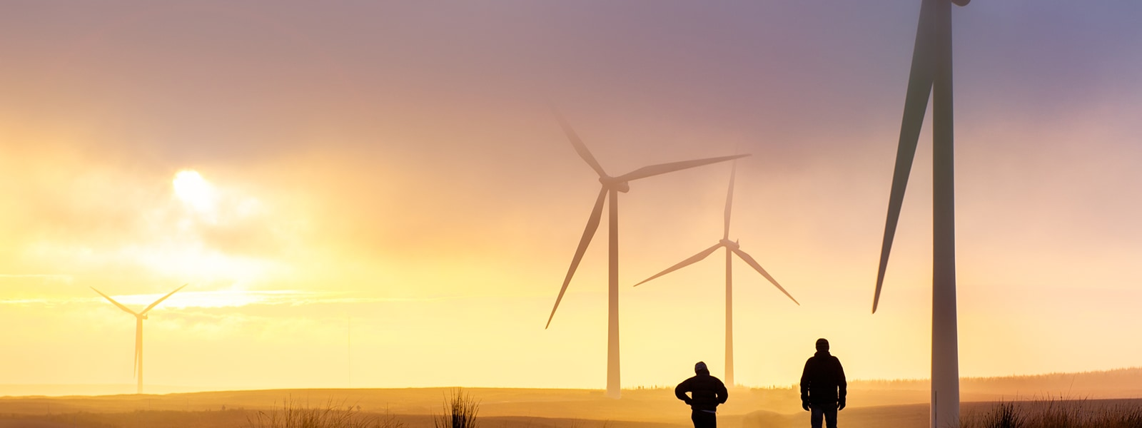 2 workers silhouetted by the sunset in front of a windfarm.