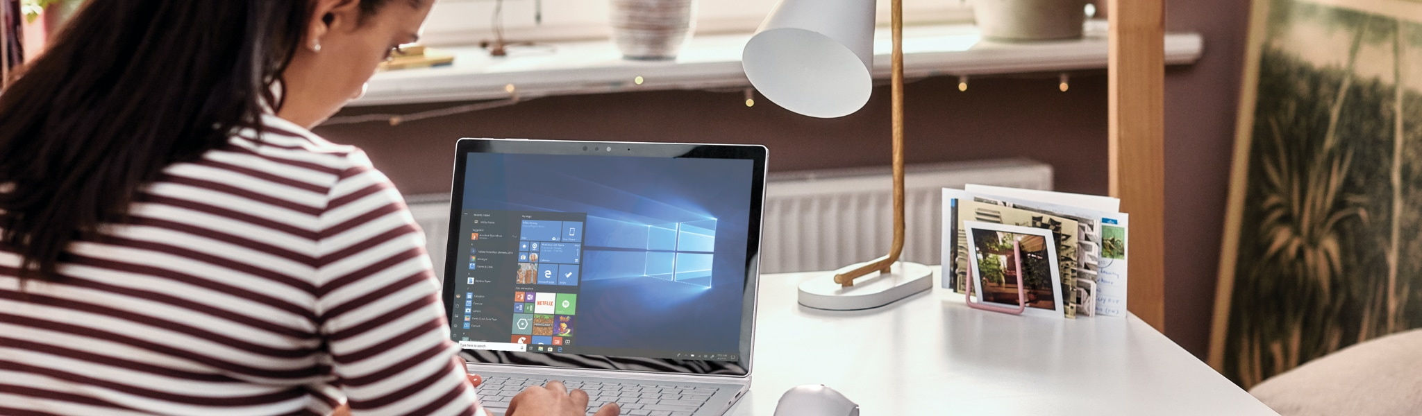 Person seated at a desk in a casual office setting working on a laptop that is displaying the Windows 10 home screen