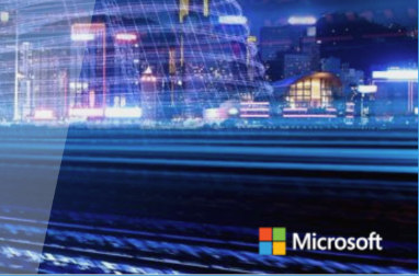 Modern buildings at night reflected from a shiny surface with the Microsoft logo
