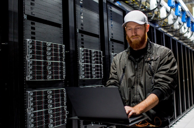 IT person working in large data center in front of stacks of servers