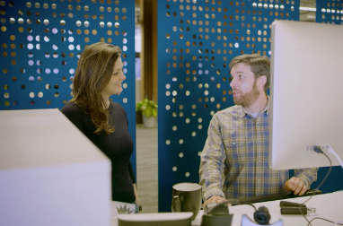 Two people standing and talking at a desk with monitors