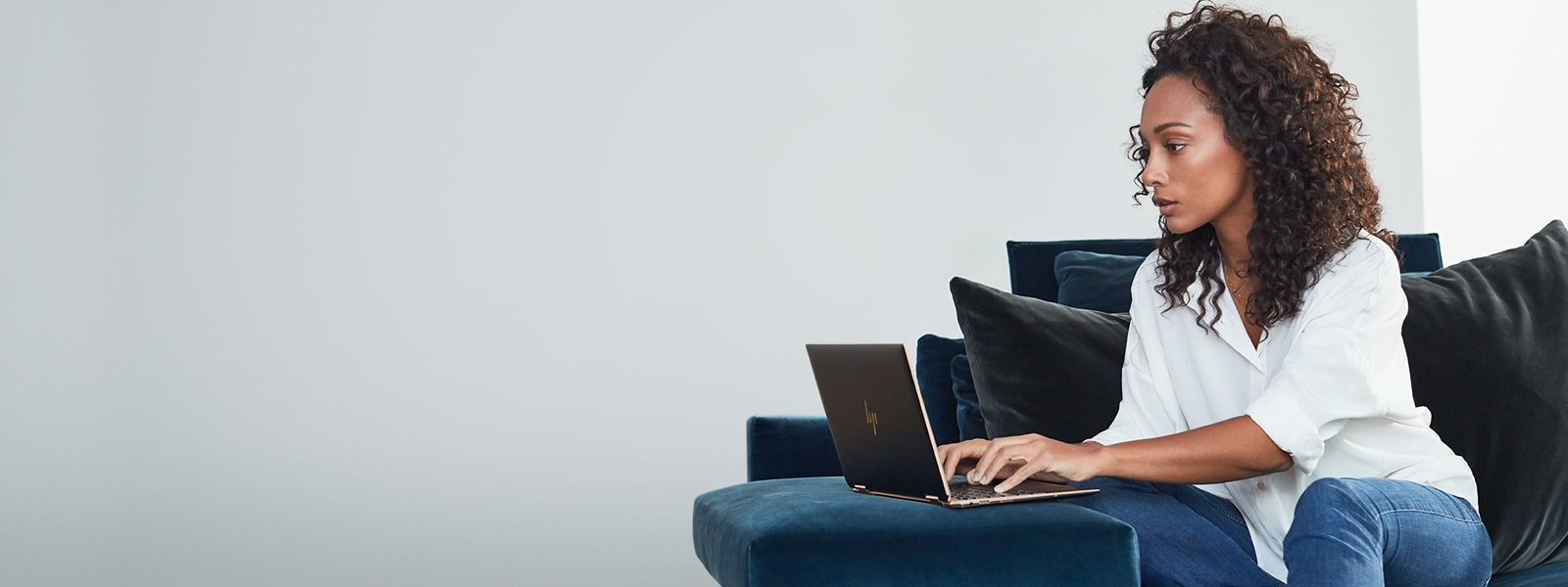 Woman sitting on a couch using a Windows 10 laptop