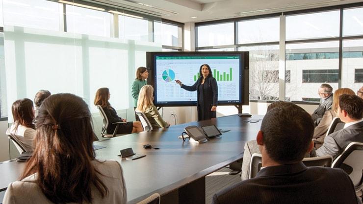 オフィスのカンファレンス ルームでエクゼクティブに対しプレゼンテーションを行う 2 人の女性