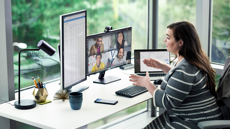Woman conducting a Microsoft Teams meeting at her desk with 3 monitors, keyboard, and mobile phone