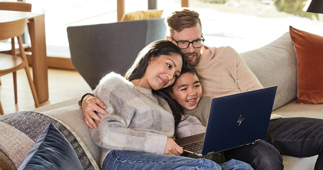 Two adults and a child snuggle on a couch while looking at something on a laptop screen and smiling.