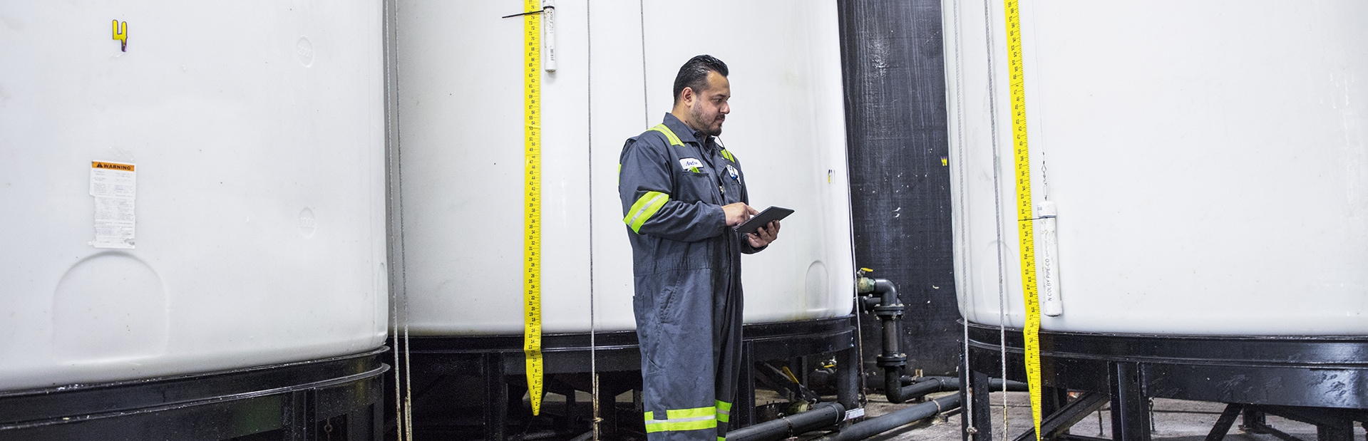 A frontline worker wearing coveralls with reflective shoulder and arm bands, using a tablet in a job site.