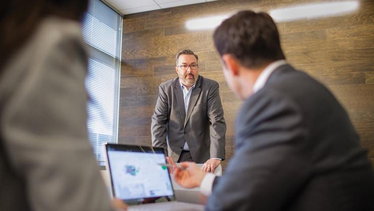 オフィスの会議室でノートパソコン上のデータを見ている 3 人のエグゼクティブ