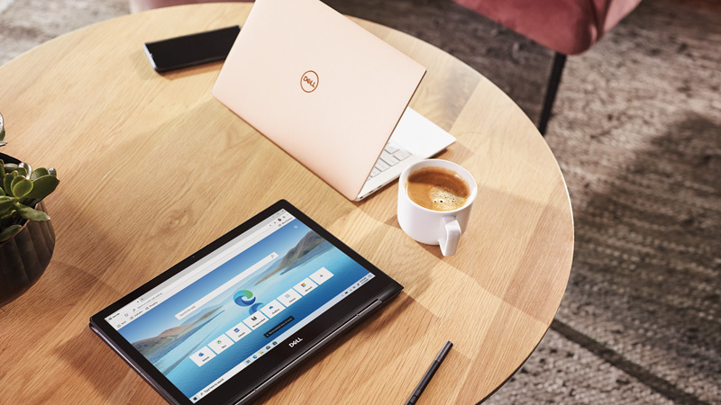 Microsoft Edge browser shown on tablet sitting on coffee table with pink laptop