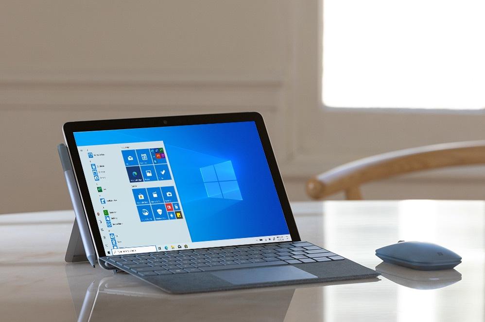 جهاز Surface Go 2 على مكتب مع Mobile Mouse يعرض شاشة بدء تشغيل Windows 10 Gmunk