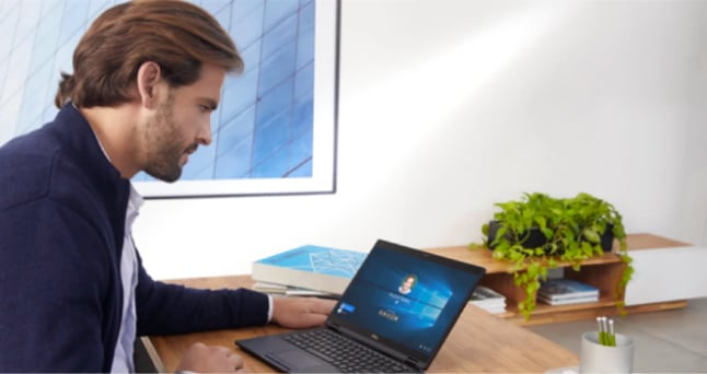 Person sitting at a desk signing in to their Microsoft account on a laptop.