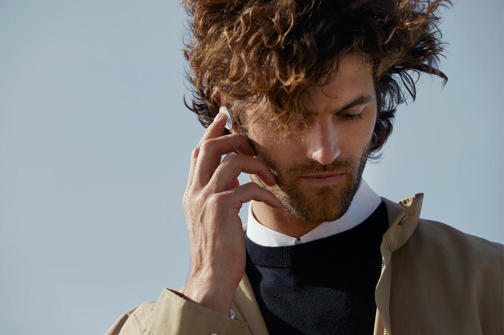 一位男士站在外面處理 Surface Pro X,同時在使用 Surface Earbuds 通話