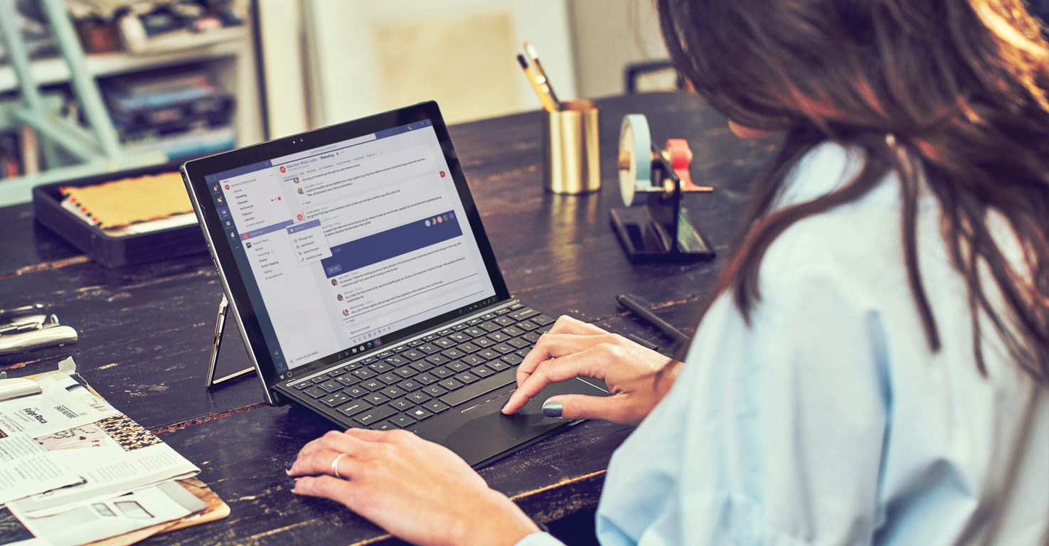 Person using Microsoft Teams on a laptop while seated at a large wooden desk in their home office