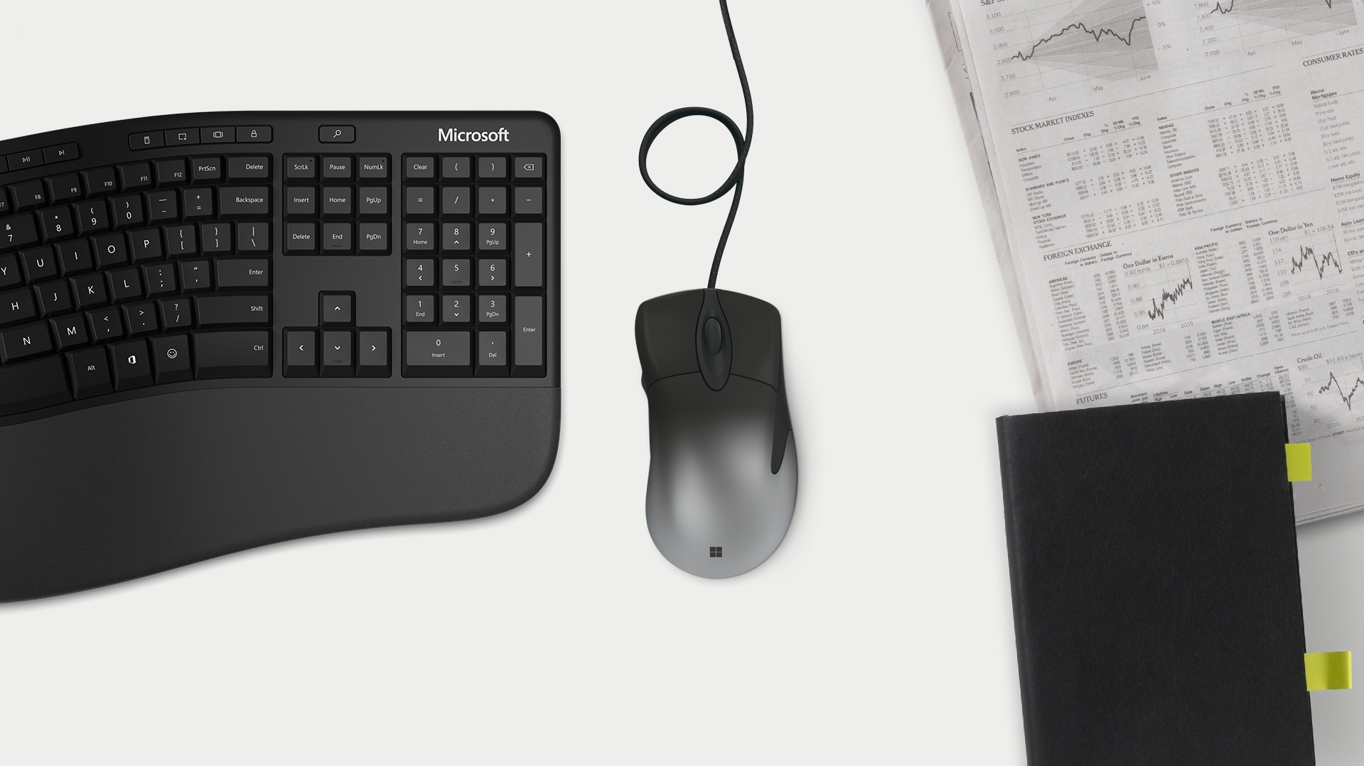 Intelli mouse and ergonomic keyboard on a table with a newspaper and a journal.