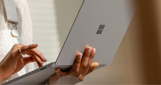 Close-up of a Surface laptop. One hand is holding the laptop as the other hand types on the keyboard.