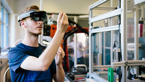A man using a HoloLens glass to experiment