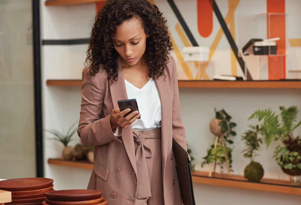 Person standing in a home furnishings retail store looking at a mobile device