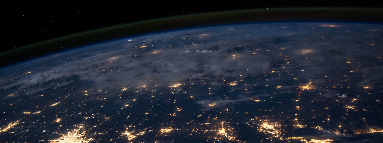 View of the Earth from space with city lights visible against dark sky