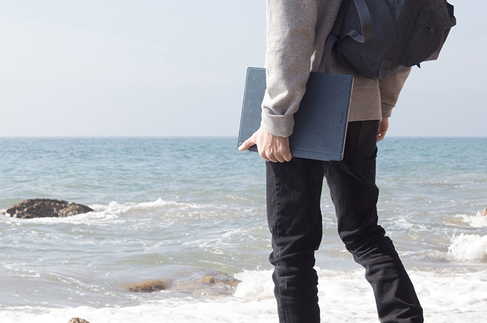 A male person at the beach, carrying a Surface Pro