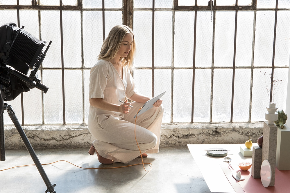 Woman staging photo session, using Surface Pro with Surface Pen
