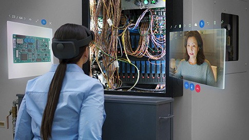 A tech woman using a HoloLens glass to work