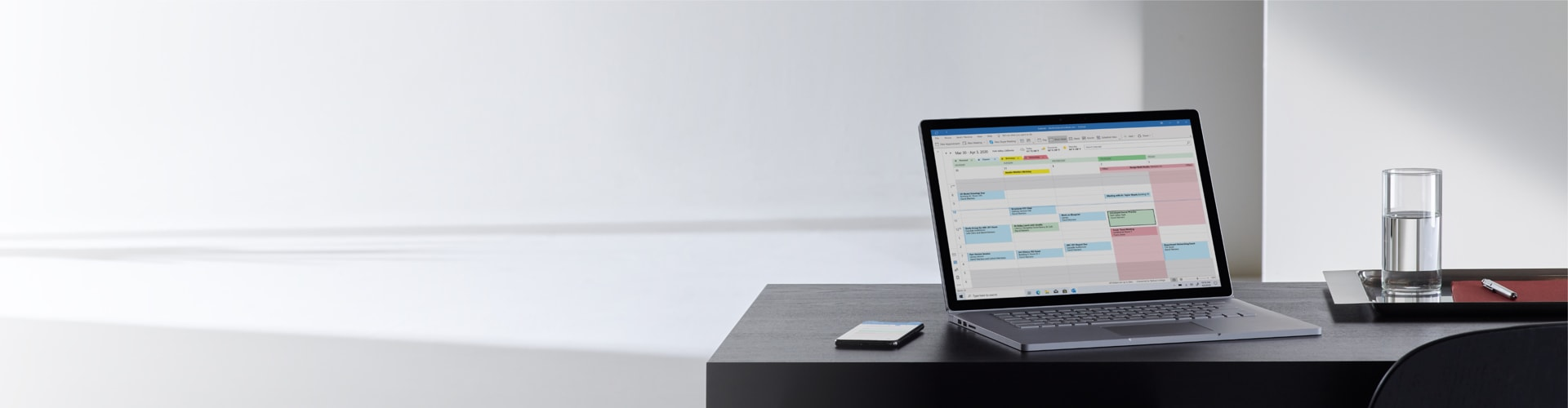 An open laptop sitting on an office desk with a mobile phone next to it. The laptop screen displays an Outlook calendar.