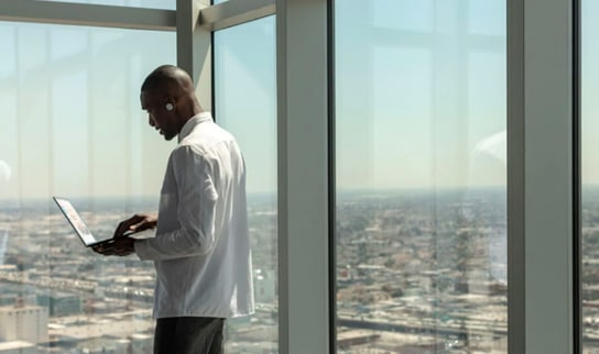 Person using a laptop and wireless earbuds while standing by large windows overlooking a city below.