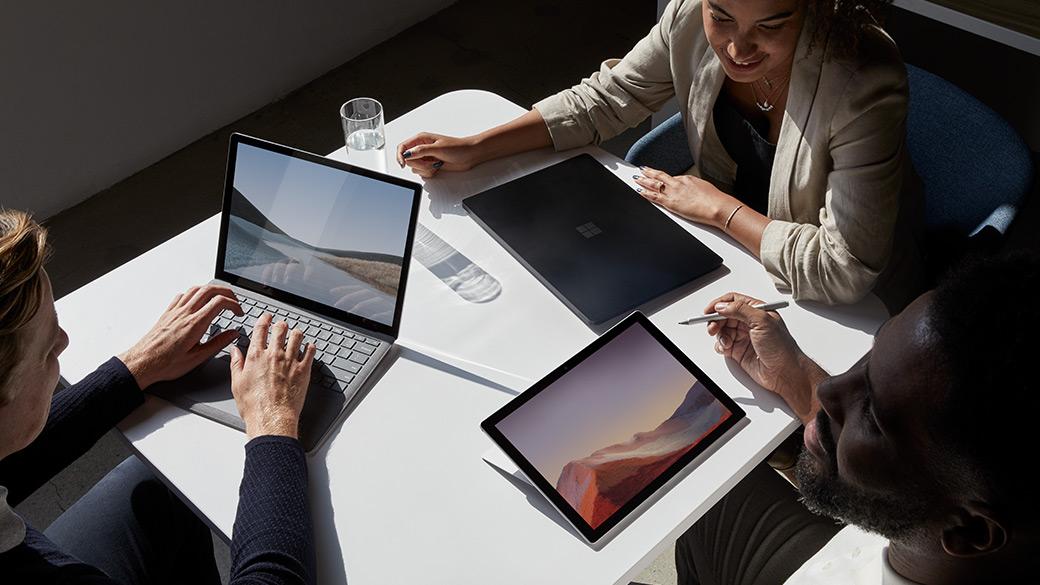En gruppe mennesker samlet rundt et bord med Surface-enhetene sine