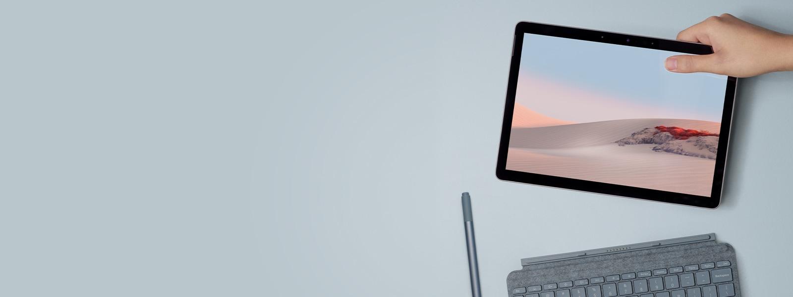 Surface Go 2을(를) 들고 있는 사람의 손, Surface 펜 및 타이핑 커버