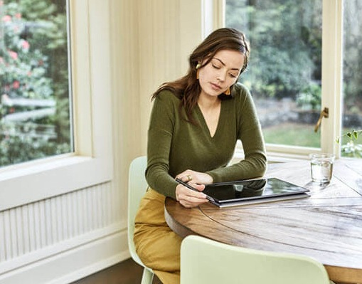 A woman sits at a kitchen table in a modern home using her Lenovo Yoga computer in tablet mode.